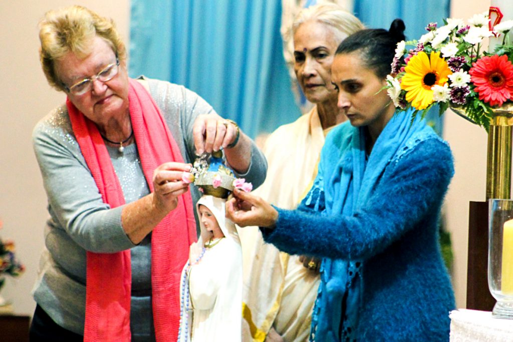 Maida Vale parishioners Betty Flynn, Luciana Sasidhran & Amber David place a crown on the top of a statue of Our Lady of Fatima during the annual Flores de May celebrations to commemorate the feast of Our Lady of Fatima. Photo: Supplied.
