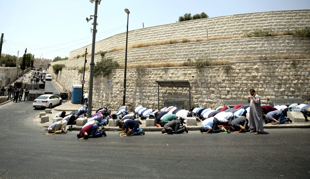 Palestinians pray on the street close to Lion's Gate in the Old City of Jerusalem on July 22. Muslims have been converging outside the gate for prayers after Israel erected metal detectors near the Al-Aqsa mosque compound, in response to a July 14 shooting. Photo:CNS/Atef Safati, EPA.