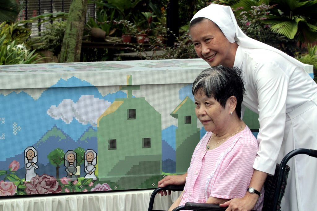 Canossian Sister Geraldine Tan, administrator of St Joseph's Home and Hospice, smiles as she pushes a patient in her wheelchair in 2010 outside the facility in Singapore. Photo: CNS/Stephen Morrison, EPA.