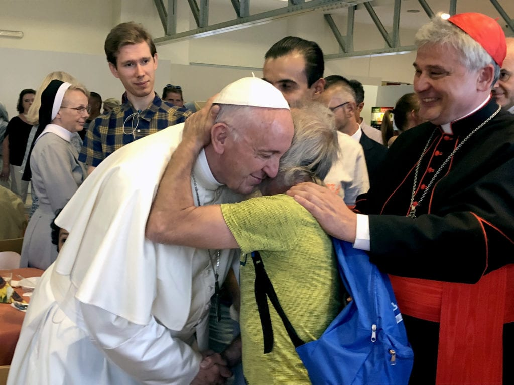 Pope Francis greets a man during a dinner for the poor hosted by new Cardinal Konrad Krajewski, the papal almoner, right, in the dining hall at the Vatican on 29 June 29. Photo: CNS/Gianna Lasilli.
