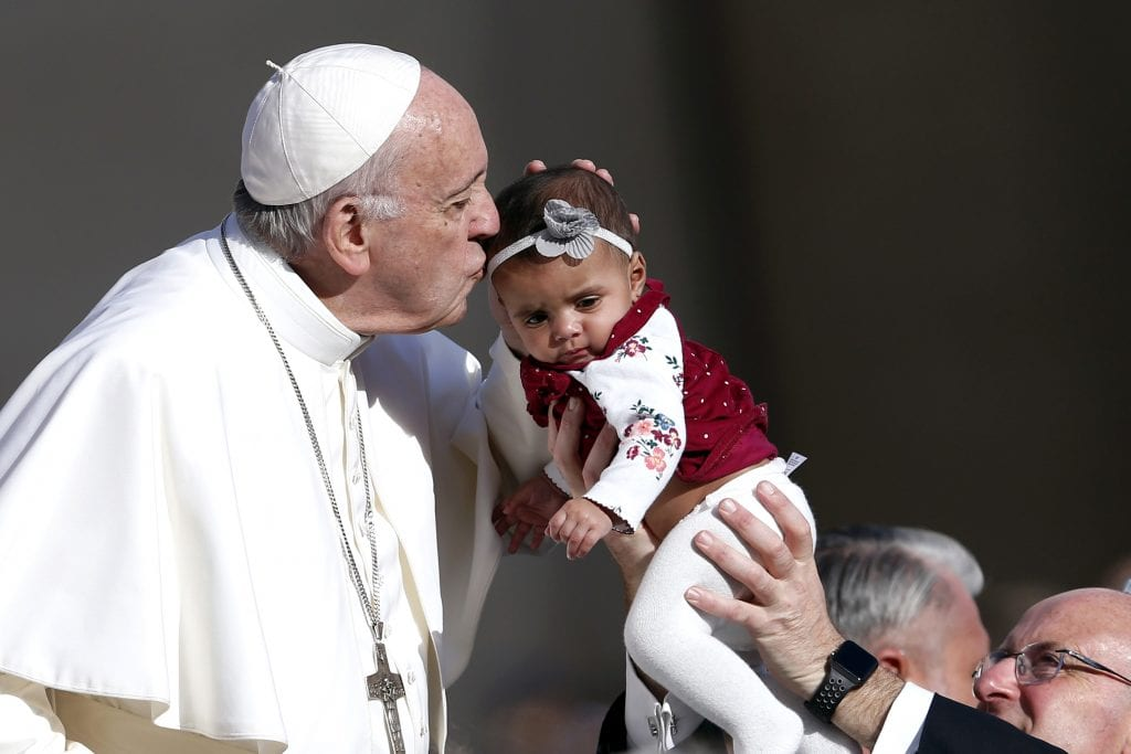 Pope Francis kisses a baby during his general audience in St Peter's Square at the Vatican on 7 November. Photo: Paul Haring/CNS.