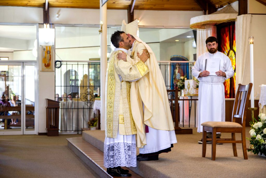 Newly ordained Deacon Chris de Sousa is embraced by Bishop Don Sproxton, moments after his parents placed a chasuble over his garments for the very first time. Photo: Matthew Lau.