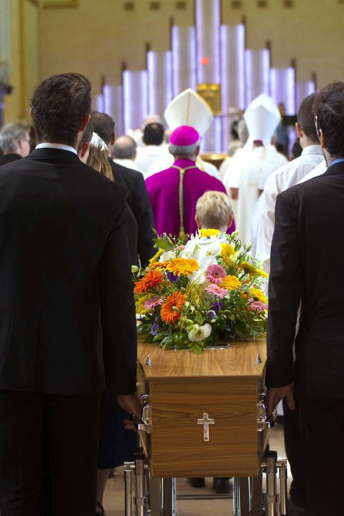 Fr Pitzen's casket is ushered into the St Mary's Cathedral by his loved ones. Photo: Josh Low.