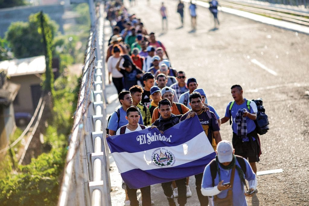 A group of Salvadoran migrants, part of a caravan traveling to the United States, walks along a road on 2 November in Tecun Uman, Guatemala. Photo: CNS/Ueslei Marcelino, Reuters.