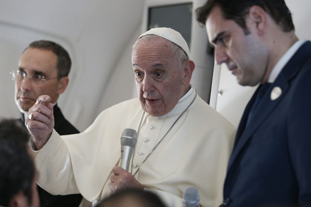 Pope Francis answers questions from journalists aboard his flight from Abu Dhabi, United Arab Emirates, to Rome on 5 February 2019. Also pictured are Msgr Mauricio Rueda, papal trip planner, and Alessandro Gisotti, interim Vatican spokesman. Photo: CNS/Paul Haring.