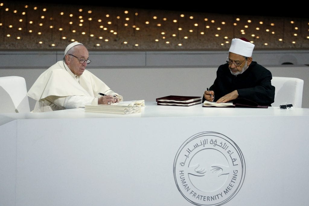 """Pope Francis and Sheik Ahmad el-Tayeb, grand imam of Egypt's al-Azhar mosque and university, sign documents during an interreligious meeting at the Founder's Memorial in Abu Dhabi, United Arab Emirates on 4 February 2019. The Holy Father and Sheik el-Tayeb stepped into a theological debate on the will of God toward religions when they signed a document on """"human fraternity"""" and improving Christian-Muslim relations. Photo: Paul Haring/CNS."""