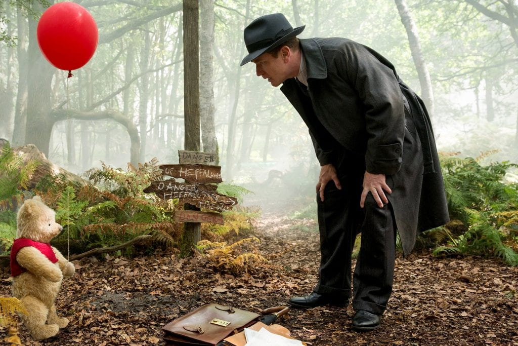 """Ewan McGregor, as Christopher Robin, shares a scene with Winnie the Pooh in the live-action adventure movie """"Christopher Robin"""". Photo: Laurie Sparham/Disney."""