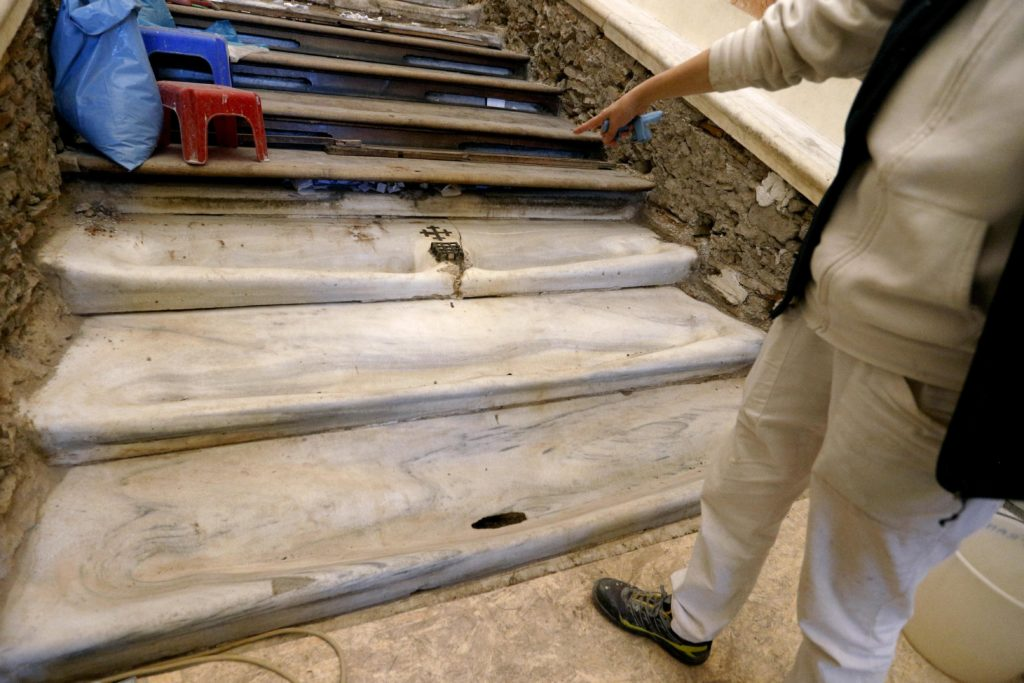 A worker points to the Holy Stairs during restoration work at the Pontifical Sanctuary of the Holy Stairs in Rome March 15, 2019. Vatican restorers have removed the wood covering the stairs, which tradition maintains Jesus climbed when Pilate brought him before the crowd. Pilgrims will have the opportunity to climb the bare marble stairs for at least a month after an April 11 unveiling of the renovated sanctuary. Photo: CNS/Paul Haring.