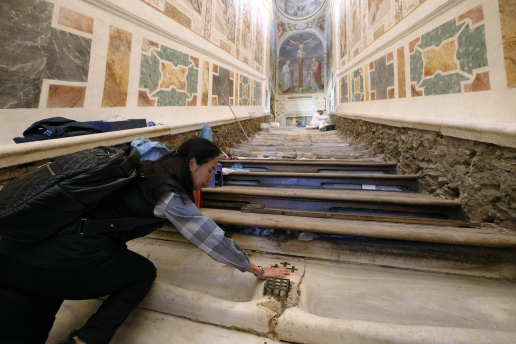 Mei Wen of Perth, Australia, touches an area of the Holy Stairs where Jesus is believed to have fallen, during restoration work at the Pontifical Sanctuary of the Holy Stairs in Rome March 15, 2019. Wen is one of the major donors who contributed to the restoration of the sanctuary. Pilgrims will have the opportunity to climb the bare marble stairs for at least a month after an April 11 unveiling of the renovated sanctuary. Photo: CNS/Paul Haring.