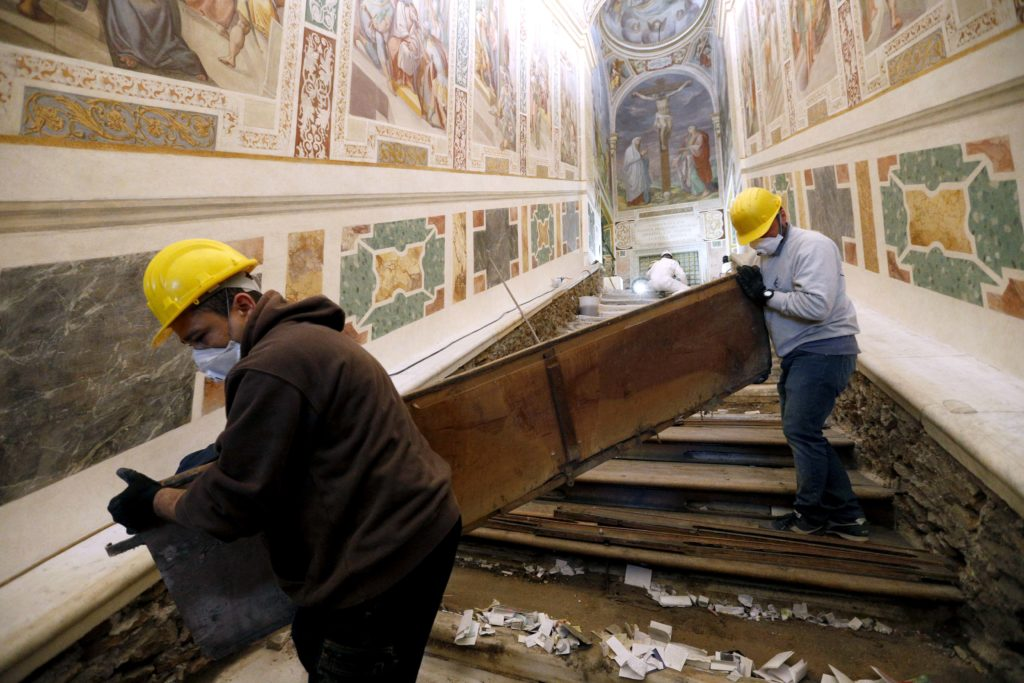 Notes from pilgrims are seen as workers remove a wooden covering over the Holy Stairs at the Pontifical Sanctuary of the Holy Stairs in Rome March 15, 2019. Pilgrims will have the opportunity to climb the bare marble stairs for at least a month after an April 11 unveiling of the renovated sanctuary. Photo: CNS/Paul Haring.