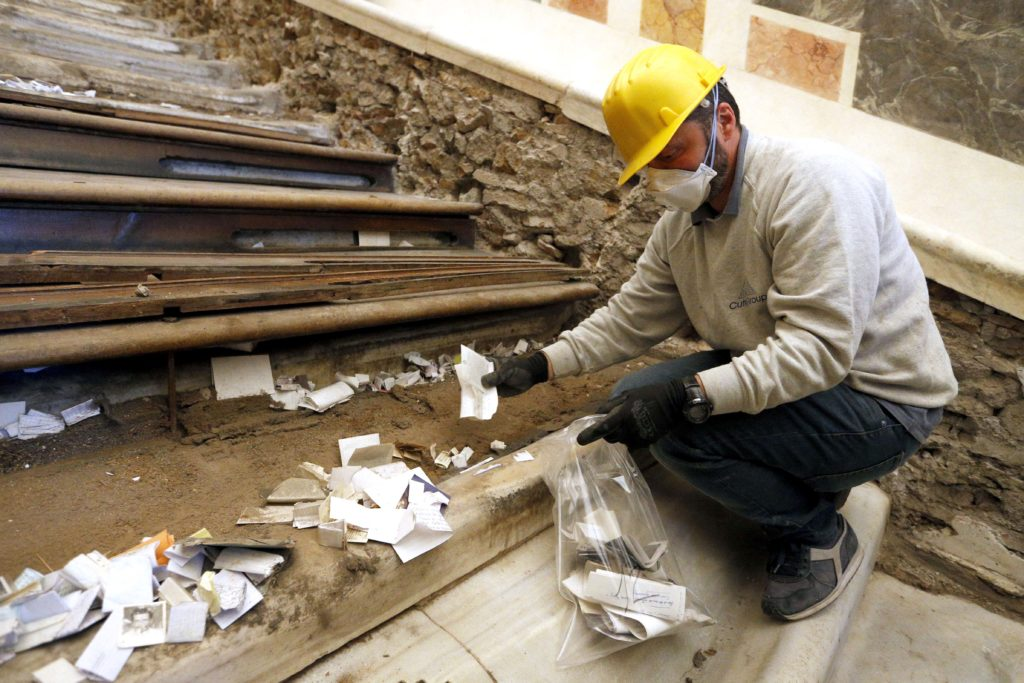 A worker collects notes from pilgrims after wooden coverings over the Holy Stairs were removed during restoration work at the Pontifical Sanctuary of the Holy Stairs in Rome March 15, 2019. Pilgrims will have the opportunity to climb the bare marble stairs for at least a month after an April 11 unveiling of the renovated sanctuary. Photo: CNS/Paul Haring.