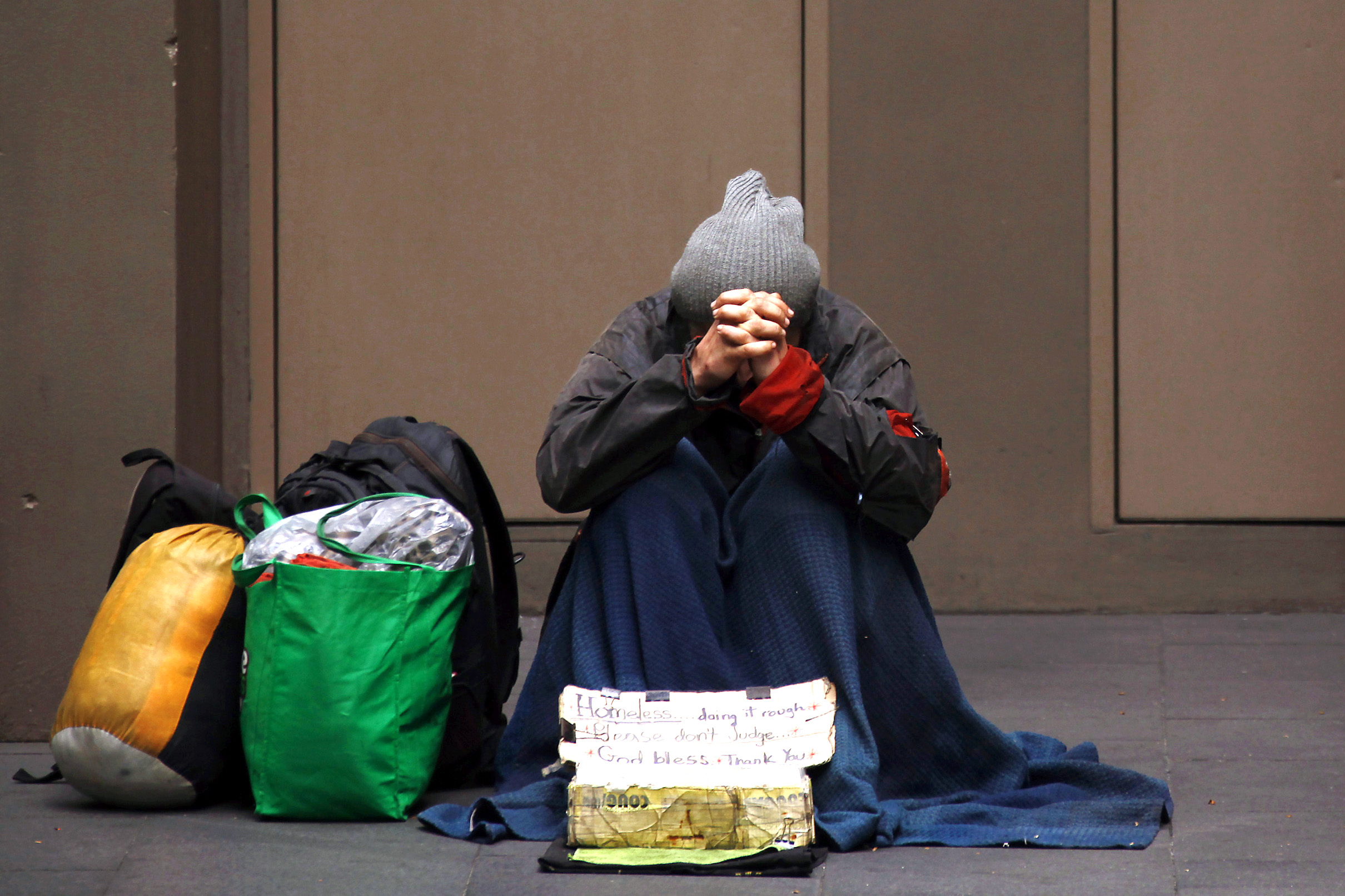 A homeless man begs for money on a street in Sydney in 2014. While Australia has one of the world's highest levels of average net wealth per person, nearly three million Australians, including more than 730,000 children, live in poverty. Photo: CNS/David Gray, Reuters.