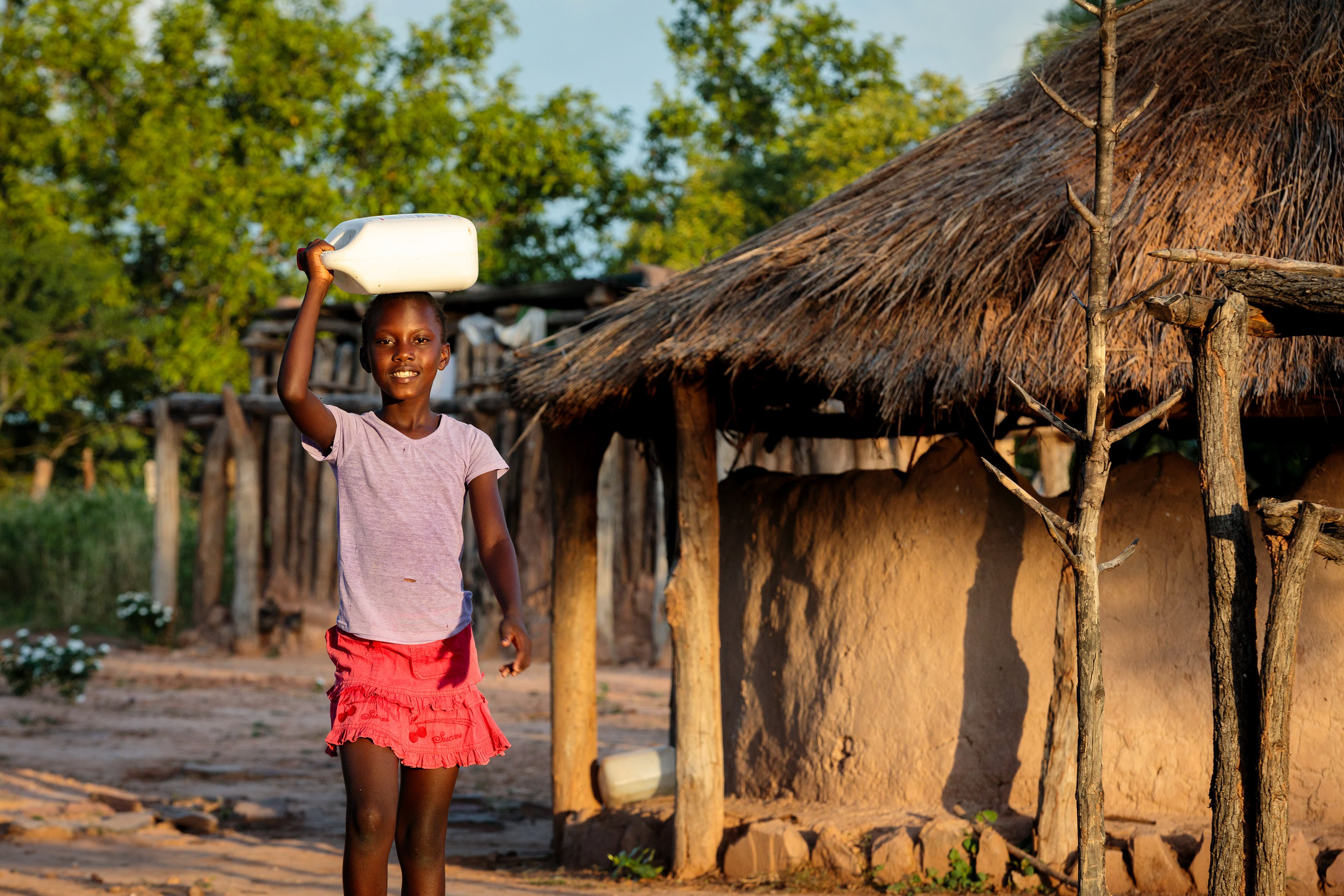 Thandolwayo outside of her home holding a 5 litre water container. Photo: Richard Wainwright/Caritas Australia.