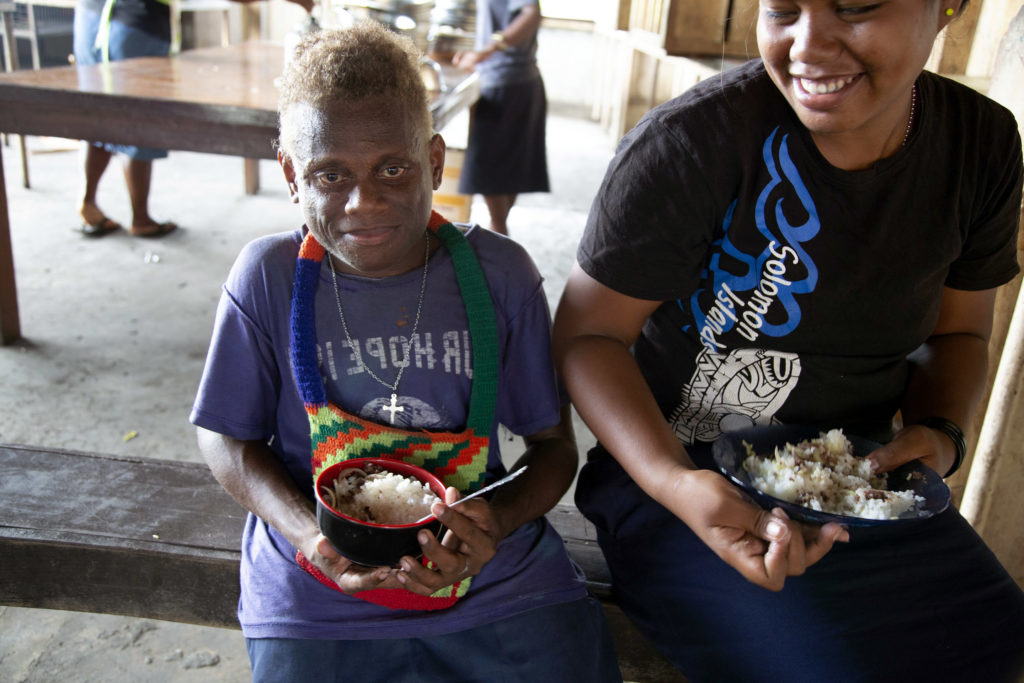 Peter and his friend eat lunch at the Aligegeo Secondary School. Photo: Cassandra Hill/ Caritas Australia.