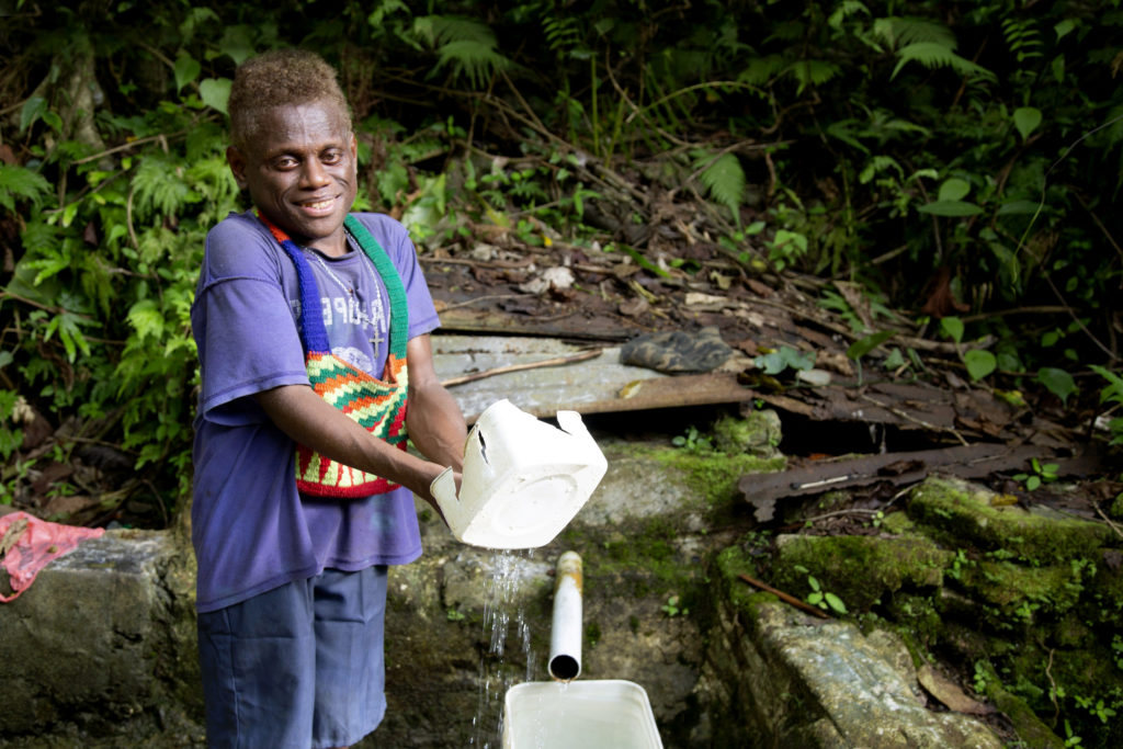 Peter bathes with water from a well about a kilometre away from his boarding school on Malaita Island, in the Solomon Islands. Photo: Cassandra Hill/Caritas Australia.