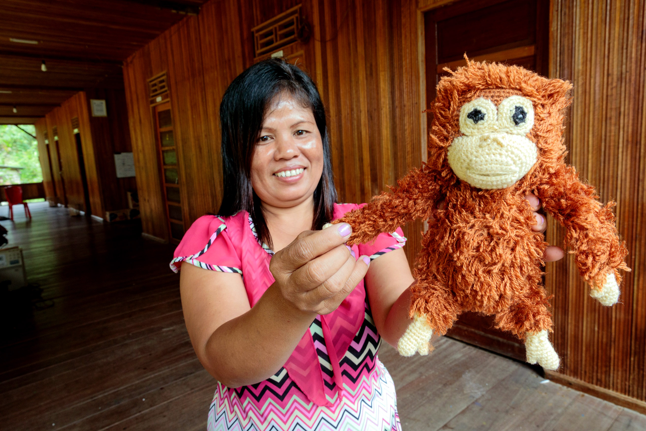 Tati on the veranda of the eco-tourism project long house showing a woollen orangutan doll she made to sell to tourists. Photo: Richard Wainwright/Caritas Australia.