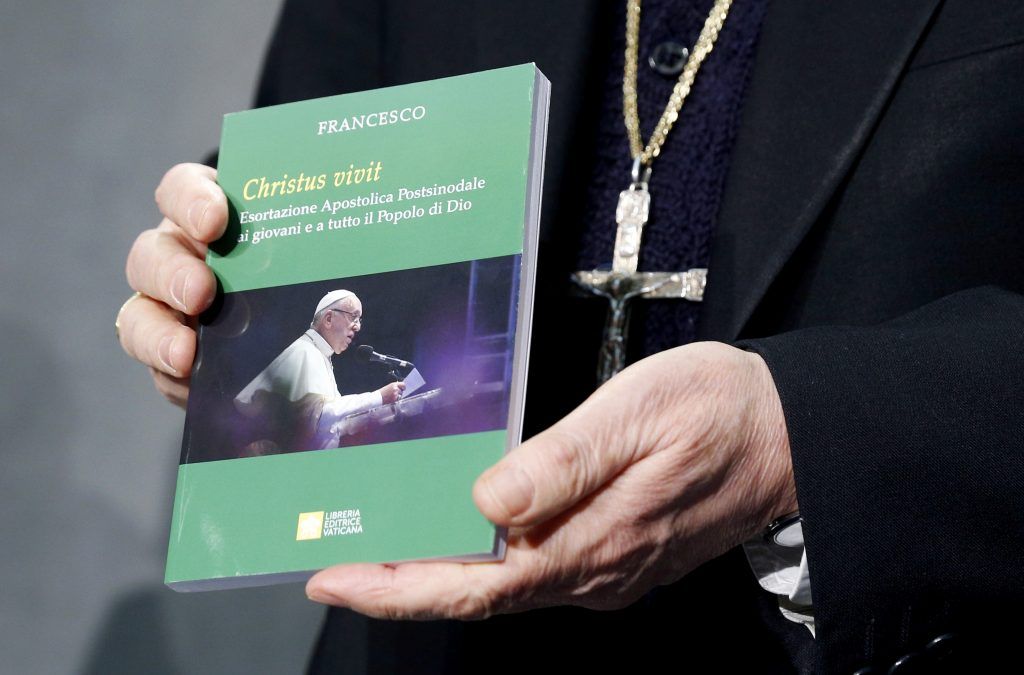"Cardinal Lorenzo Baldisseri, Secretary-General of the Synod of Bishops, holds Pope Francis' Apostolic Exhortation, ""Christus Vivit"" (Christ Lives), during a news conference for its presentation at the Vatican 2 April, 2019. The document contains the Pope's reflections on the 2018 Synod of Bishops on young people, the faith and vocational discernment. Photo: CNS/Paul Haring."
