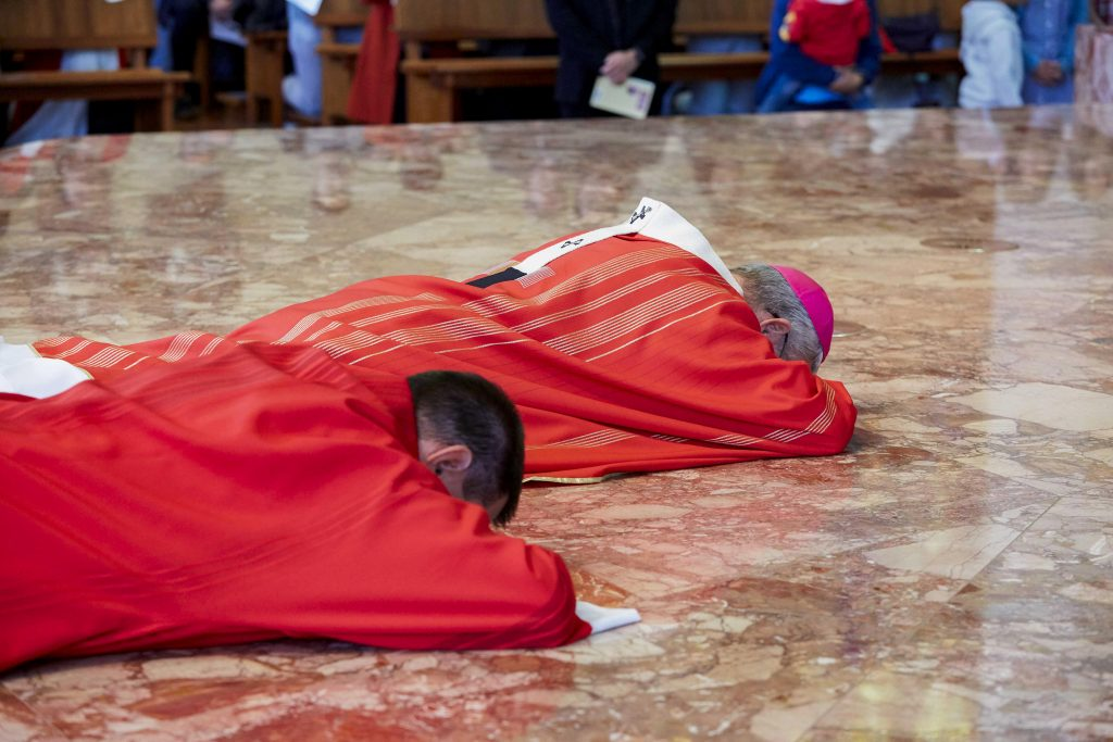 Archbishop Costelloe prostrates on the altar at the start of the Lord's Passion on Good Friday 2019. Photo: Ron Tan.