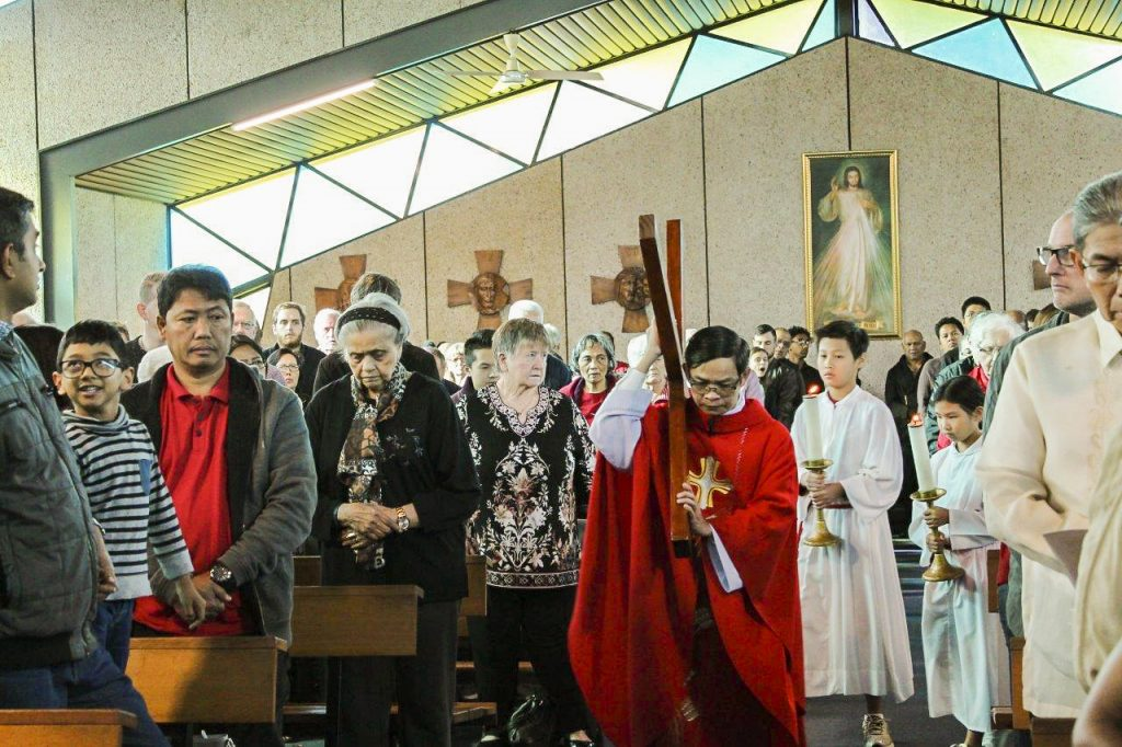 Fr Quynh carries a cross down the aisle during the Lord's Passion. Photo: Sunil Rodrigues.