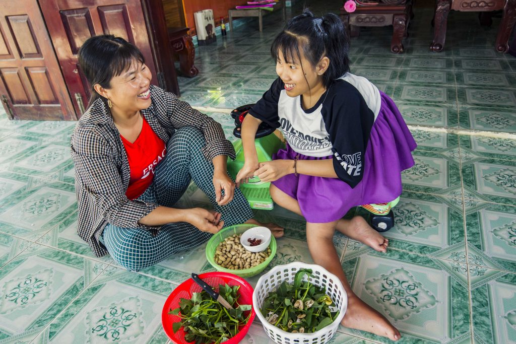 Nguyet helping her mother with cooking. Photo: Nguyen Minh Dinc/Caritas Australia.