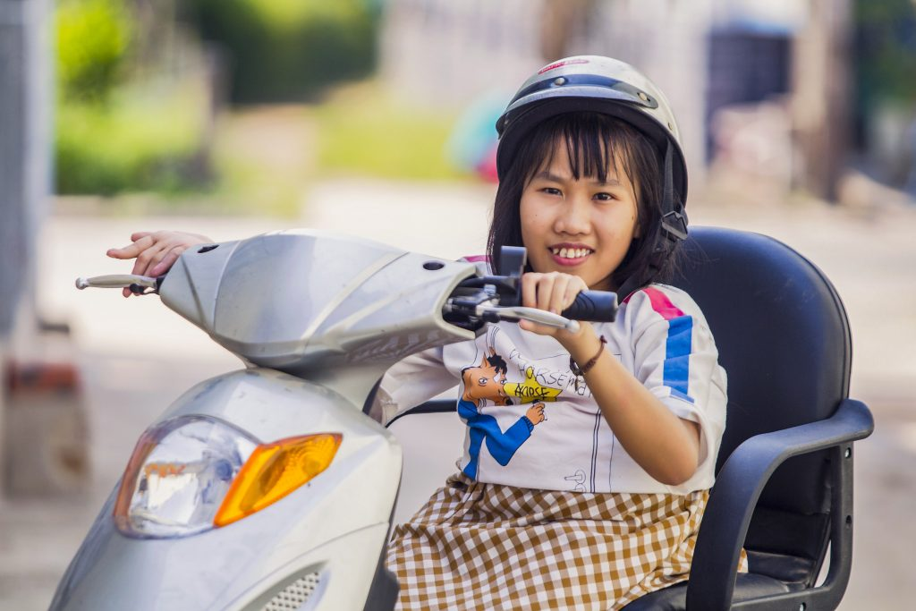 Nguyet on her motorbike she purchased with the income from her business. Photo: Nguyen Minh Dinc/Caritas Australia.