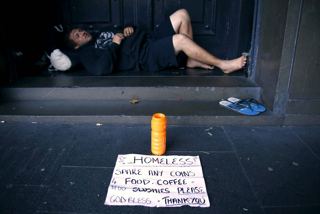 A man rests in the doorway of a building. Photo: David Gray, Reuters.