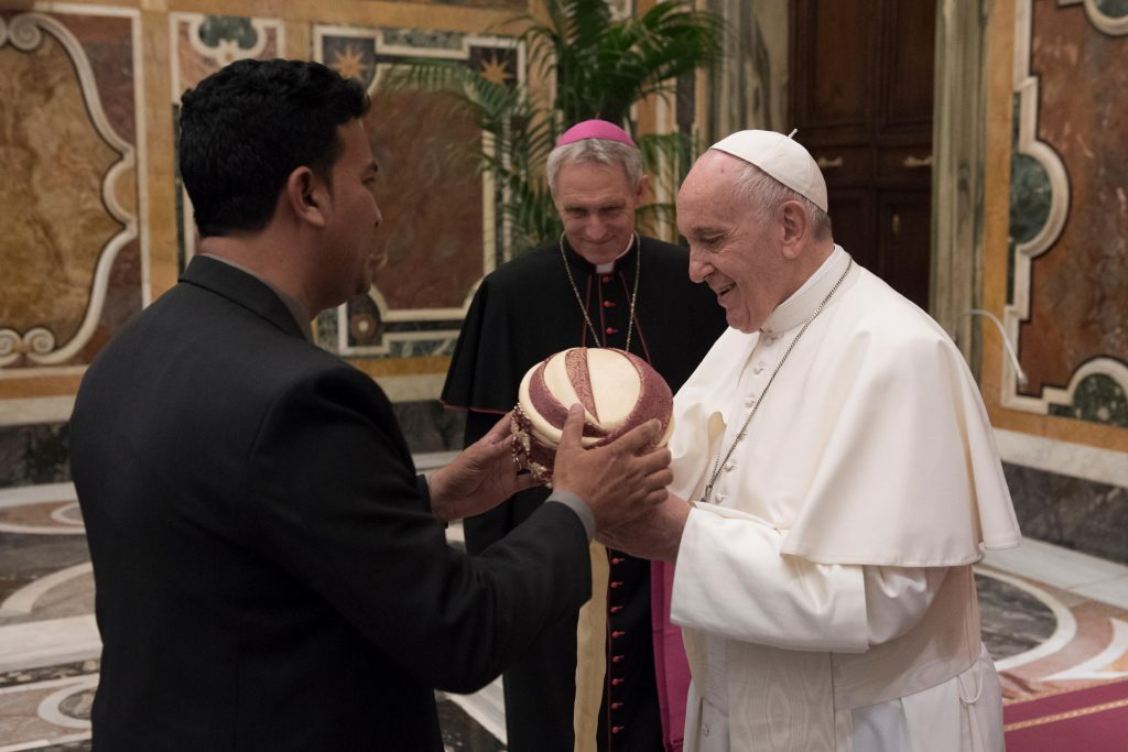 Pope Francis is presented with a turban during a meeting on 26 April at the Vatican with members of the Catholic Biblical Federation. At centre is Archbishop Georg Ganswein, prefect of the papal household. Photo: Vatican Media/CNS.