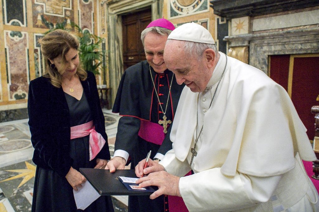 Pope Francis signs his press identification card as Associated Press journalist Patricia Thomas and Archbishop Georg Ganswein, Prefect of the Papal Household, look on during an audience with members of the Foreign Press Association of Italy, at the Vatican on 18 May 2019. Photo: Vatican Media/CNS.