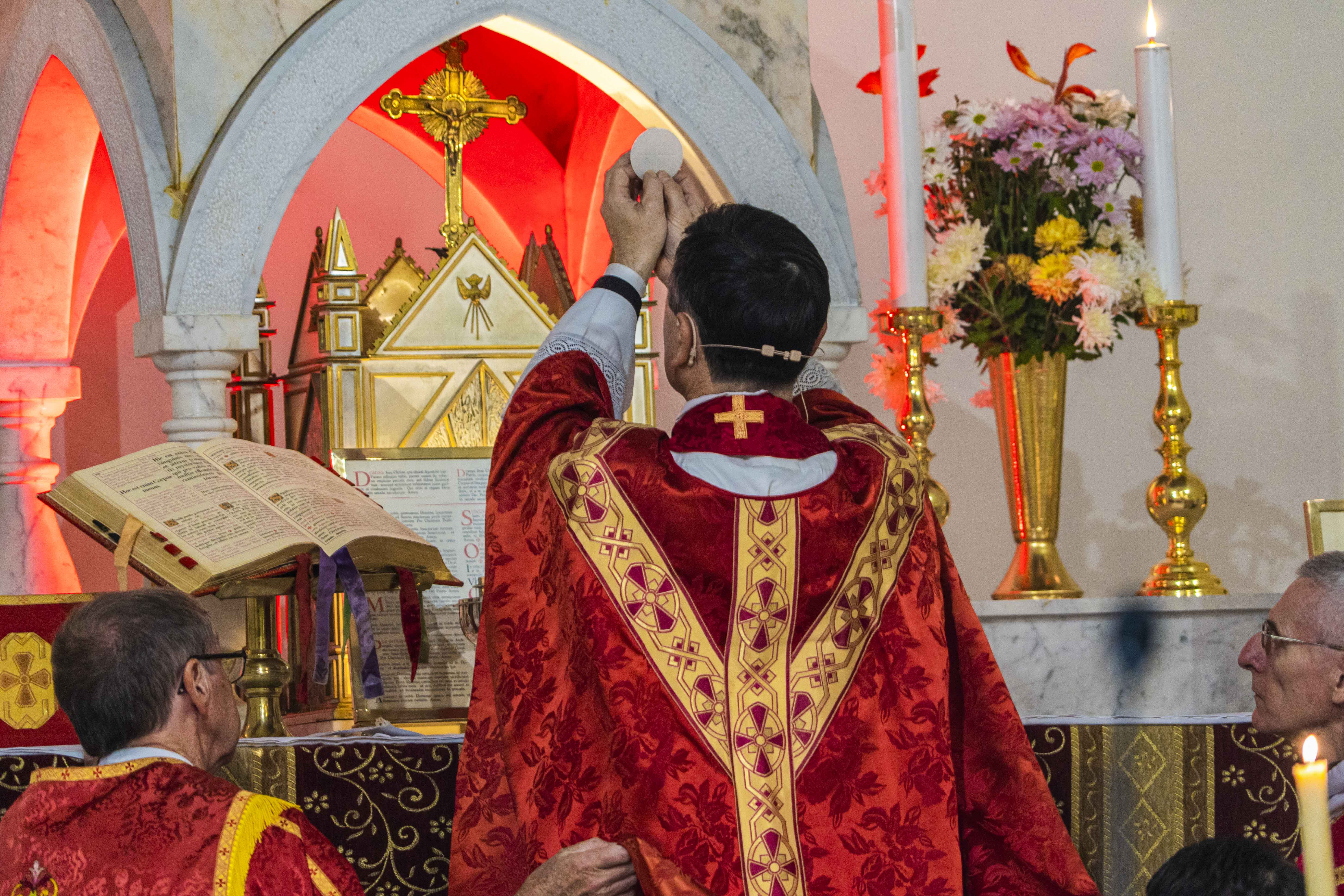 Fr Rowe elevates the Eucharist during the Mass to celebrate his 25 years of the priesthood. Photo: Josh Low.