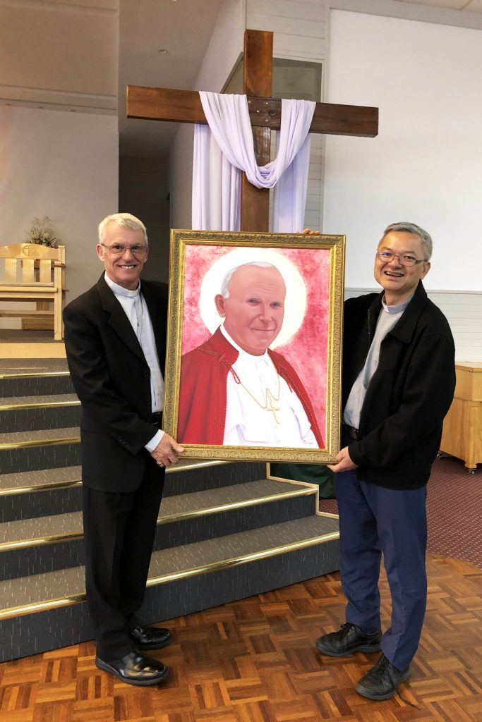 Archbishop Timothy Costelloe SDB pictured with Fr Vinh Dong and the portrait of Saint John Paul II. Photo: Supplied.
