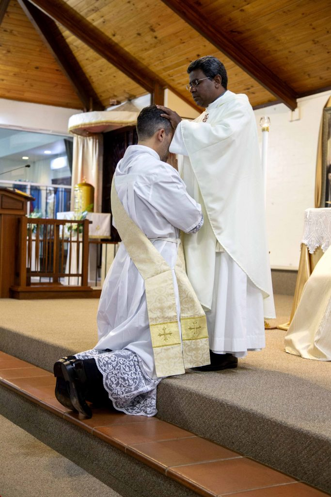 Fr Johnson Joseph CRS lays his hands in prayer on now Fr Chris' head during the Rite of Ordination. Photo: Jamie O'Brien.