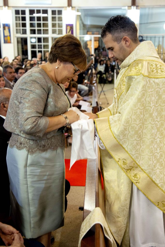 Maria De Sousa receives the maniturgium from Fr Chris and wipes the holy oil from his anointed hands, in a tradition that pays respect to the role a mother has in a priest's life. Photo: Jamie O'Brien.