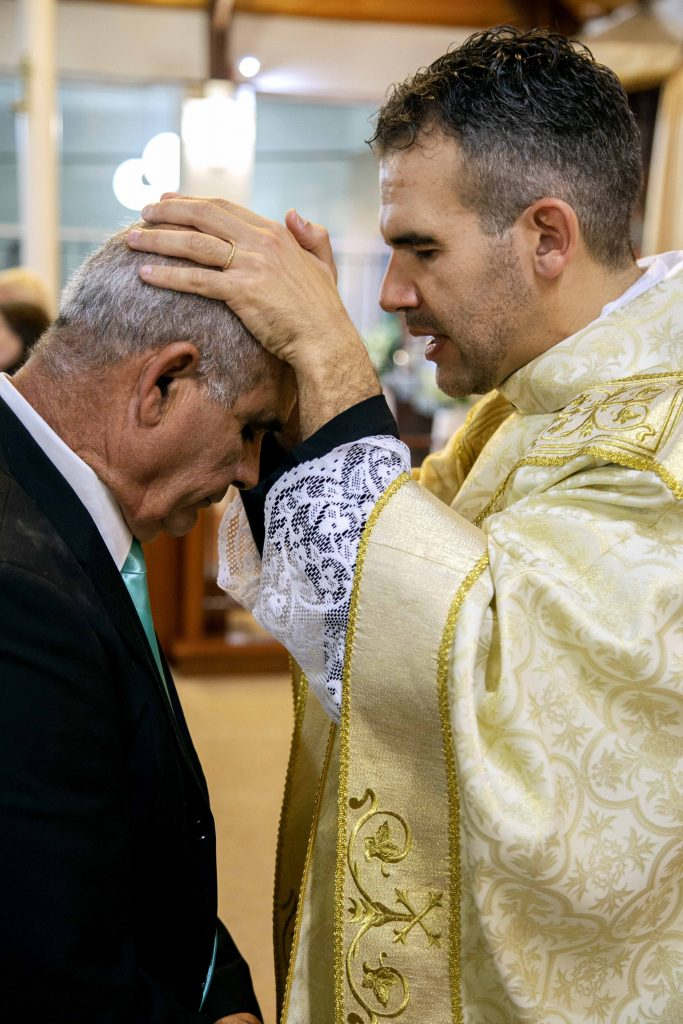 Fr Chris lays his hands on the head of his father, Joao Luis De Sousa, to impart a priestly blessing immediately after his Mass of Ordination to the Priesthood on Saturday evening. Photo: Jamie O'Brien.