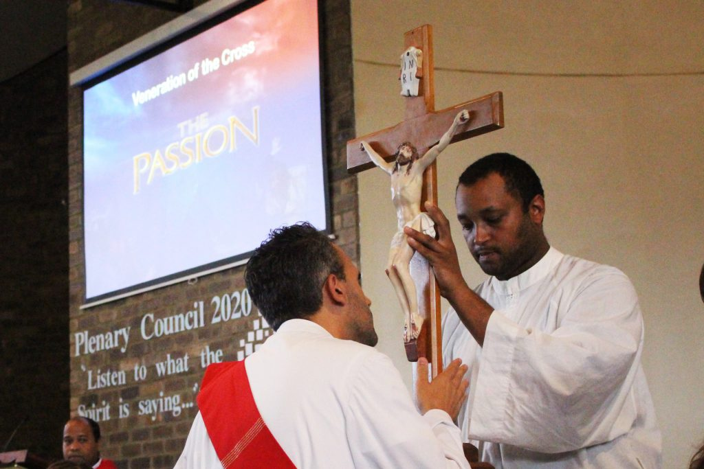 Soon-to-be-priest Deacon Chris de Sousa CRS kisses the feet of Jesus during the veneration of the Cross at OLOL Church on Good Friday, 19 April. Photo: Supplied.