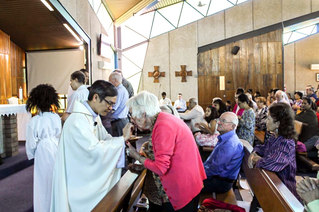 Sheelah Rudman receives Holy Communion from Fr Michael Quynh Do at Notre Dame Church in Cloverdale. Photo: Sunil Rodrigues.