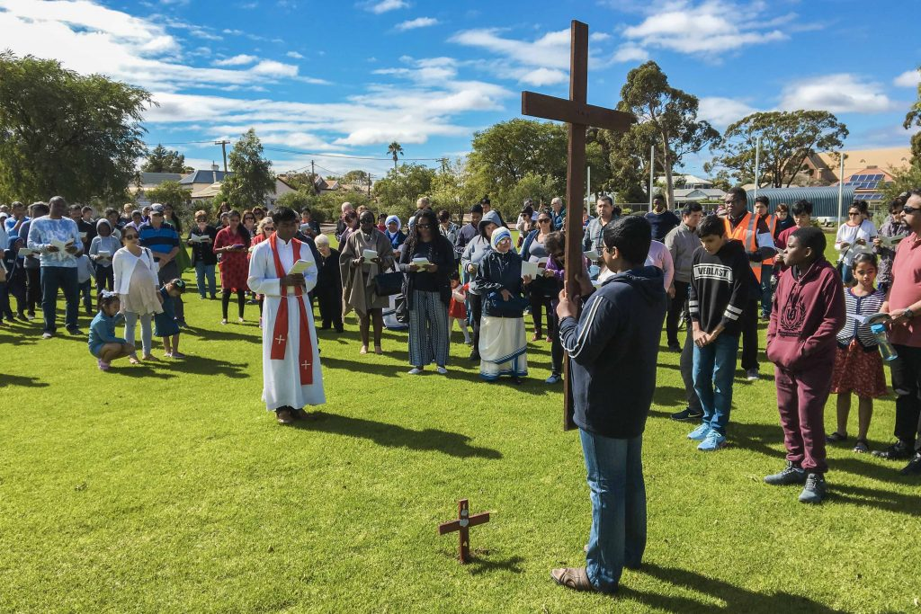 St Mary's Church Assistant Parish Priest Fr Renald Anthony is seen standing before the cross, carried by a young parishioner on Good Friday, 19 April. Photo: Robert Hicks.