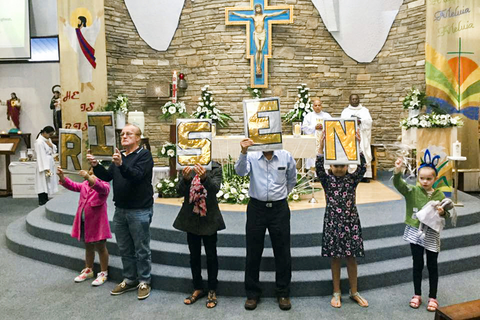 Parishioners of St Francis Assisi Church hold up letters that spell out that Christ has RISEN. Photo: Supplied.