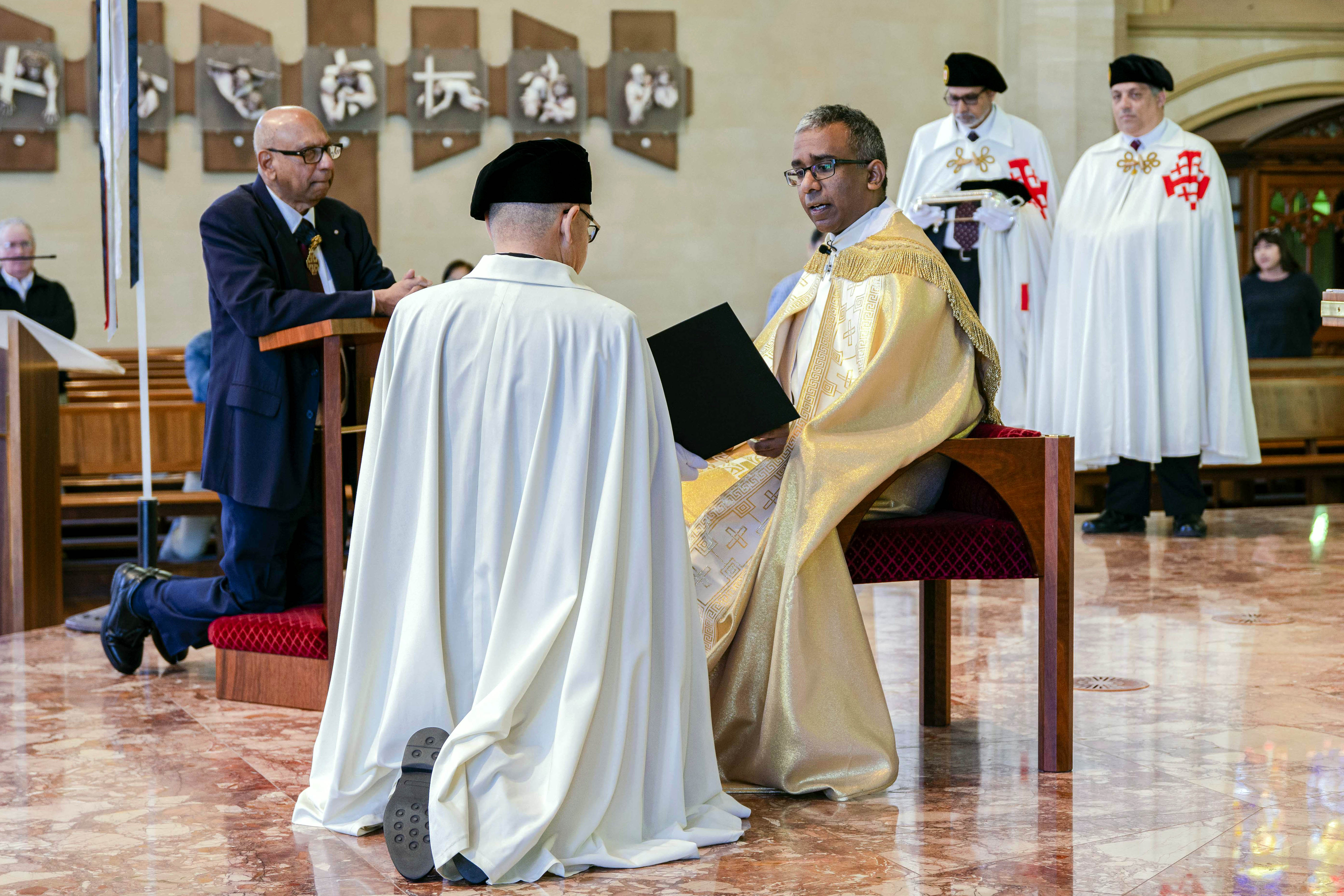 Keven Susai KCHS and Incumbent Lieutenant Jack Gardner KCHS kneel before the Altar at St Mary's, addressed by Cathedral Dean Fr Sean Fernandez. Photo: Eric Martin.