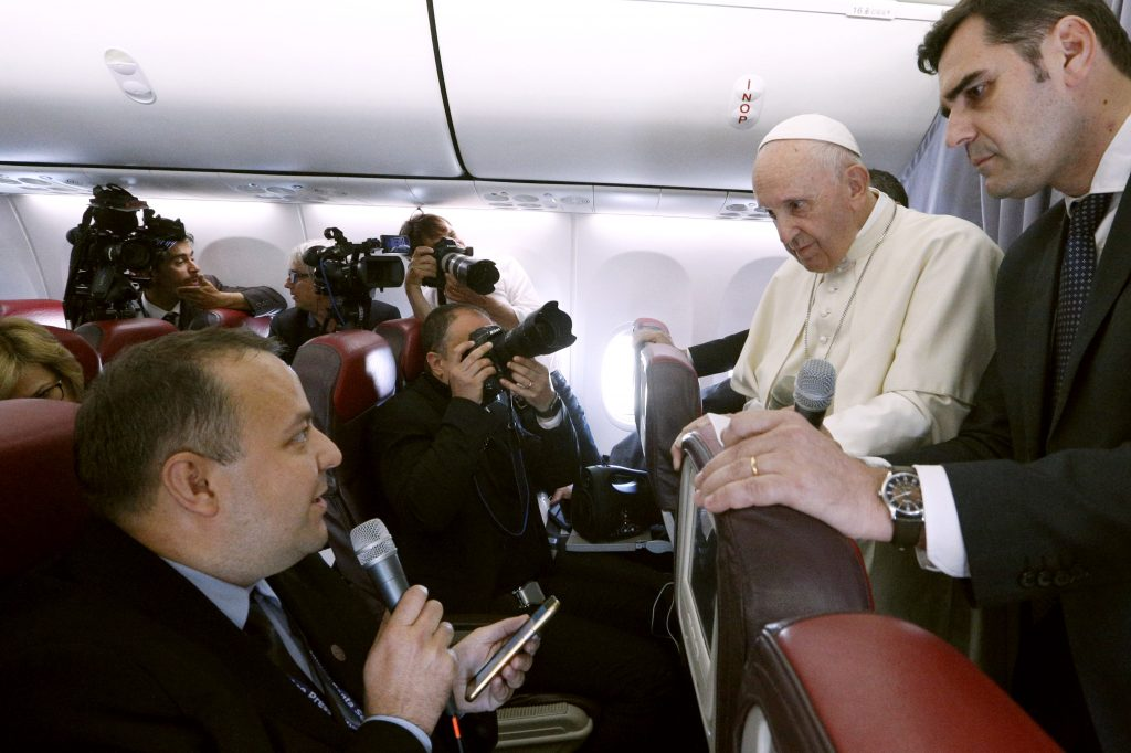 Pope Francis listens to a question from Romanian journalist Cristian Micaci aboard his flight from Sibiu, Romania, to Rome on 2 June. Photo: Paul Haring/CNS.