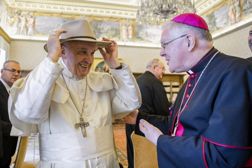 Pope Francis tries on a hat presented by Archbishop Mark Coleridge, during a meeting with Australian bishops on their Ad Limina visit to the Vatican on 24 June 2019. Photo: CNS /Vatican Media.