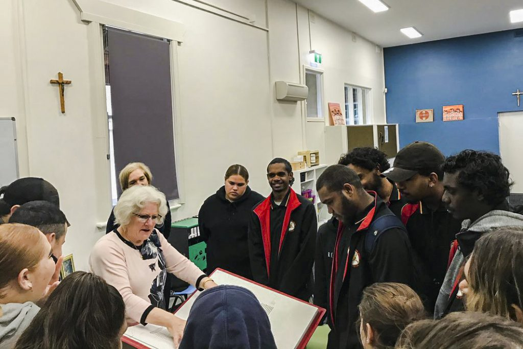 Dr Angela McCarthy explains and displays the Saint John's Bible, the first handwritten Bible in over 500 years, to a group of Year 12 students. Photo: Supplied.
