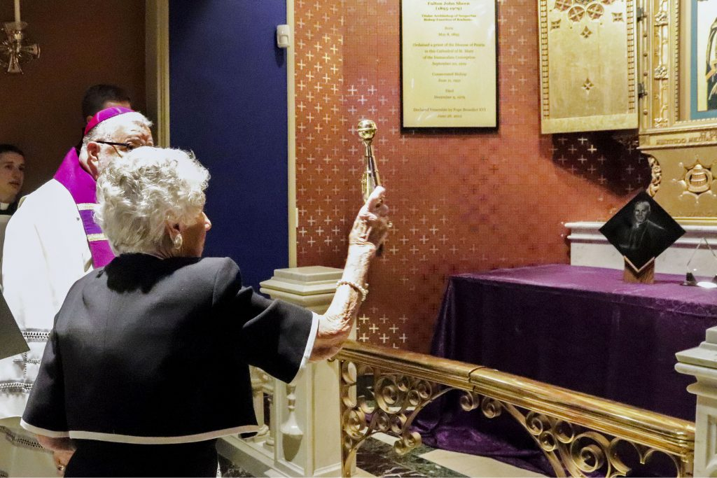 Bishop Daniel R Jenky of Peoria Ill, looks on as Joan Sheen Cunningham, niece of the late Archbishop Fulton J Sheen, sprinkles holy water on the new tomb bearing the remains of her uncle at St Mary's Cathedral in Peoria on 27 June 2019. Archbishop Sheen's remains were transferred from St Patrick's Cathedral in New York City to the Peoria cathedral. Photo: Jennifer Willems/The Catholic Post.