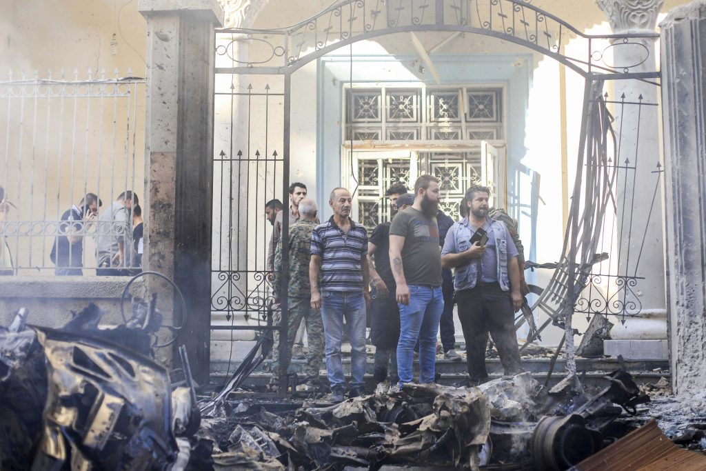People gather at the site of a car bomb blast outside the Syriac Orthodox Church of the Blessed Virgin Mary in Qamishli, Syria on 11 July 2019. Photo: Rodi Said/Reuters.