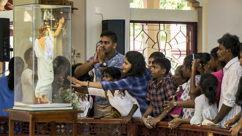 CAPTION (ACN-20190722-89394) Sri Lankans venerating and praying in front of the statue of Christ that is marked with the blood of the victims of the Easter Sunday attacks. It is now surrounded by glass and venerated in memory of those that lost their lives whilst worshipping on Easter Sunday 2019. Photo: Bartek Zytkowiak/Aid to the Church in Need.