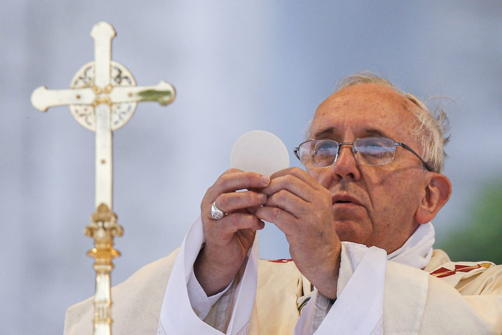 In this 2014 file photo, Pope Francis elevates the Eucharist as he celebrates Mass on the feast of Corpus Christi outside the Basilica of St John Lateran in Rome. Photo: Paul Haring/CNS.