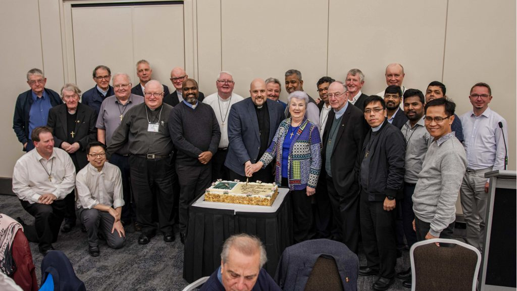 The Oblates gather around Provincial Fr Christian Fini OMI, for the cutting of the cake. Photo: Eric Martin.