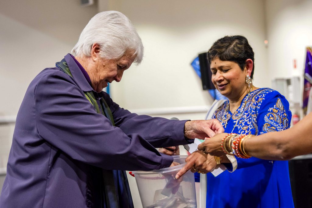 One of the guests draws a raffle ticket during the ACRATH Bollywood themed dinner to raise funds for victims of human trafficking on 10 August at Aranmore Catholic Primary School. Photo: Feby Plando.