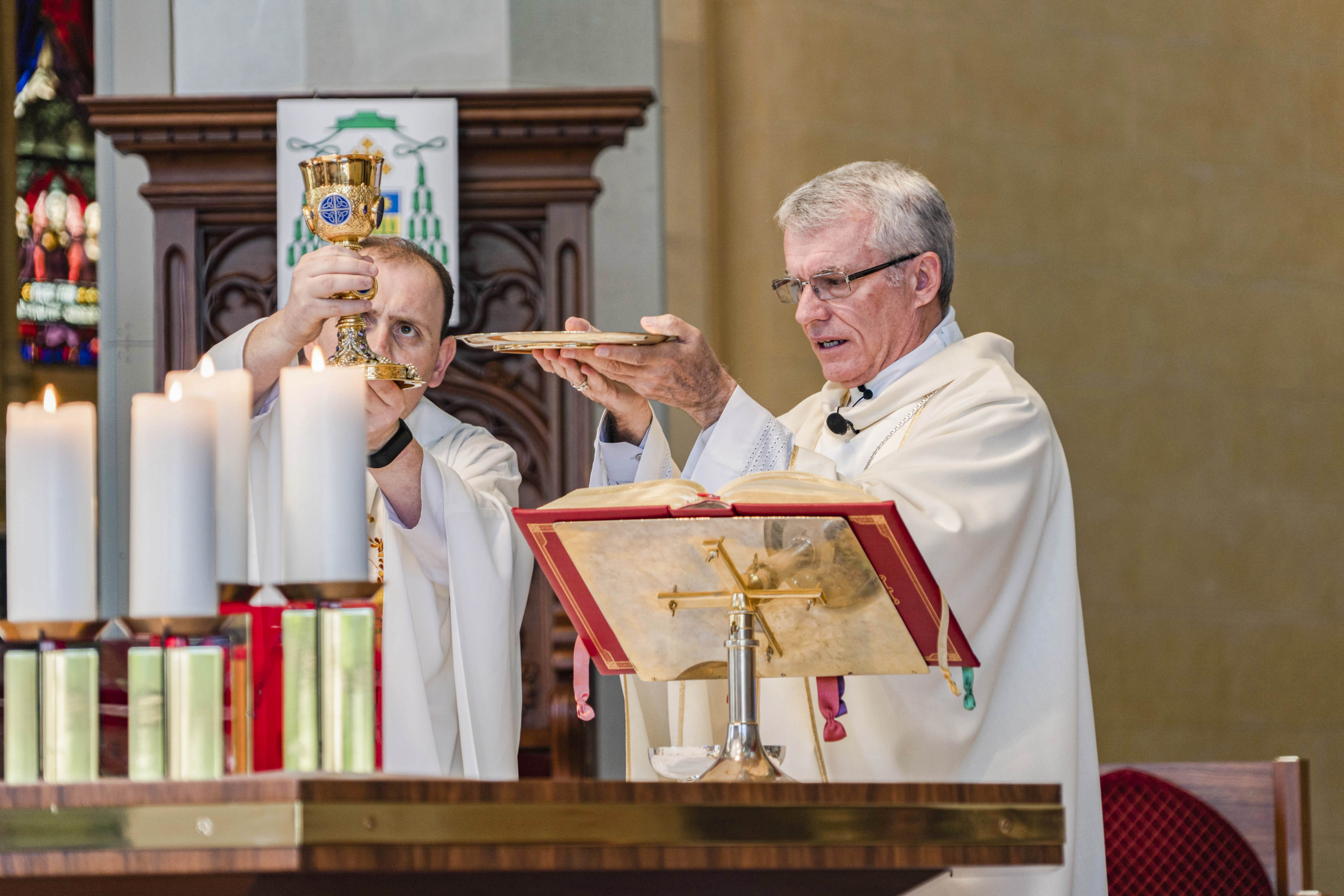 Perth Archbishop Timothy Costelloe (right) consecrates the Blessed Sacrament alongside St Mary's Cathedral Assistant Priest Fr CJ Millen on the Feast of Don Bosco, 31 January 2019. Photo: Feby Plando.