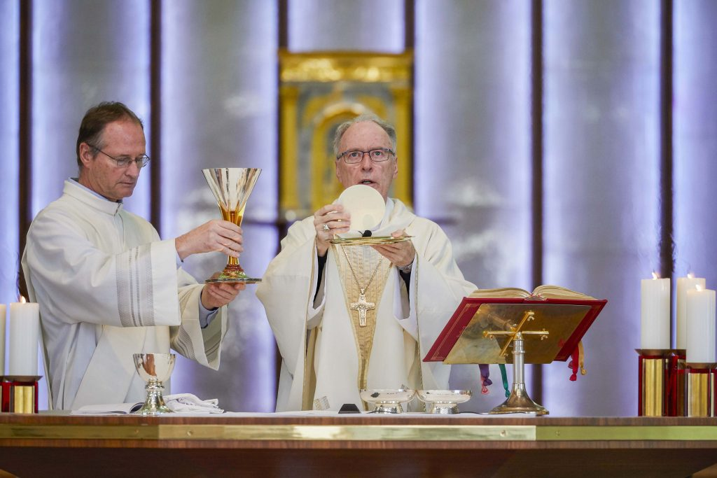 Auxiliary Bishop of Perth Donald Sproxton elevates the Eucharist as Deacon Gregory Lowe holds the chalice during the Archdiocesan Agencies Mass at St Mary's Cathedral on 23 July 2019. Photo: Ron Tan.
