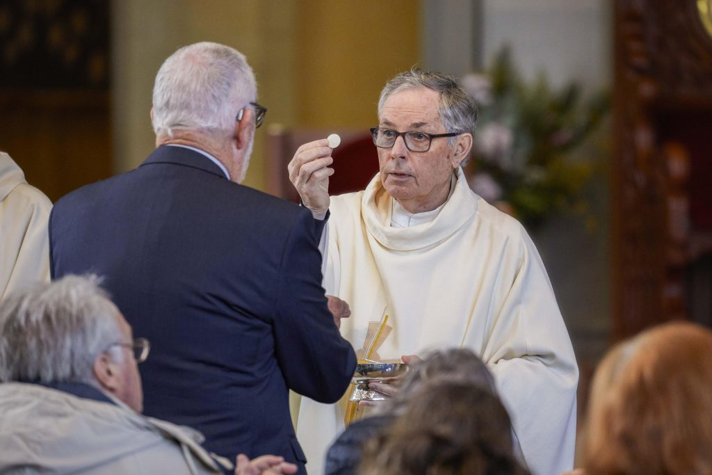 Father Brian McKenna distributes Holy Communion to a receiver. Photo: Ron Tan.